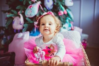 Toddler girl sitting in baby bassinet