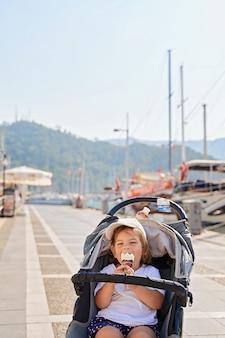 Девочка малыша сидит в коляске с мороженым. путешествие с ребенком. летнее путешествие