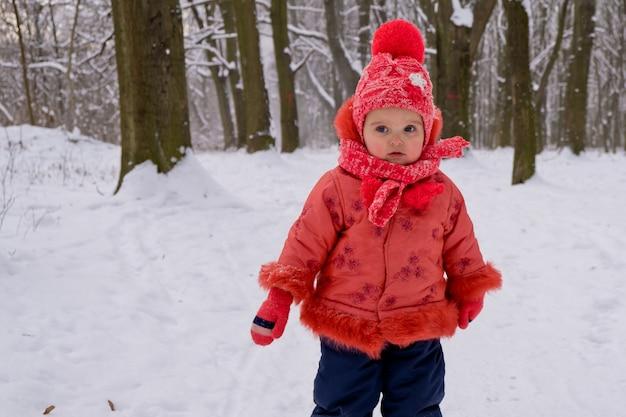 公園で雪の中を歩く幼児の女の子。霜の降る冬の季節。