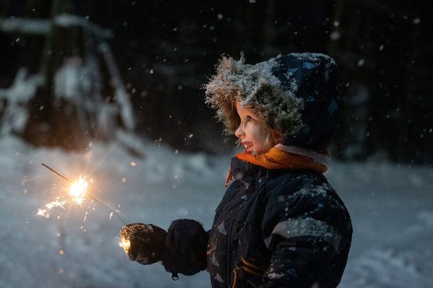 Toddler girl in winter clothes walking outside and holding sparkler in her hand. it is dark and snowy, girl is happily smiling. magic winter holidays mood