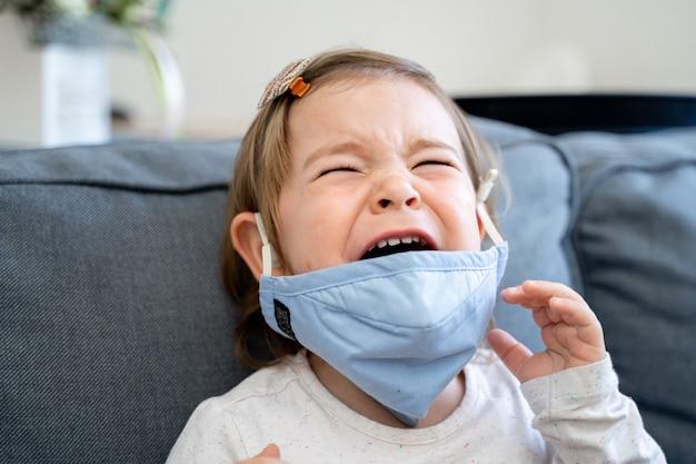 Малыш девушка с медицинской маской на лице. вспышка коронавируса