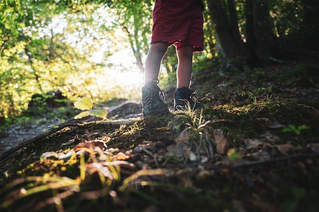 Toddler in hiking shoes standing on hiking trail