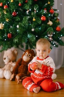 赤と白のクリスマスカバーオールの幼児は、クリスマスツリーの前にリンゴを持っています。高品質の写真