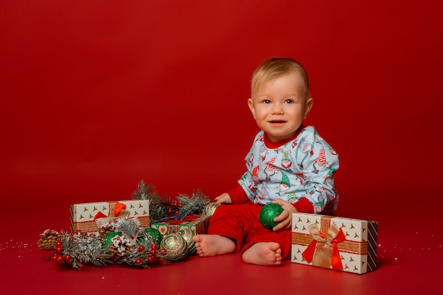 Малыш в рождественской пижаме на красном фоне, место для текста