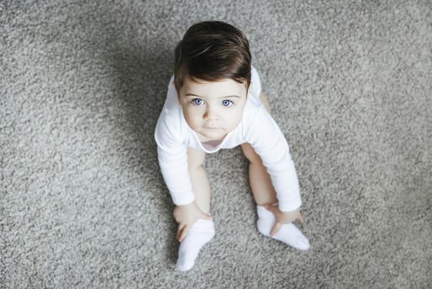 카펫에 앉아 흰색 bodysuit에서 유아 아이