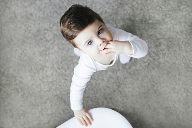 카펫에 서있는 흰색 bodysuit에서 유아 아이