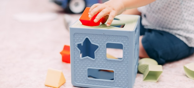 Toddler kid solves sorter puzzle block at home
