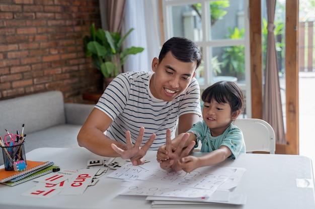 Малыш учится математике и считает с отцом