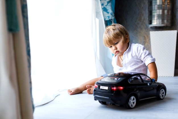 Toddler little boy playing with a big black toy car at home focus on the child