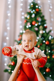 Toddler in a red-and-white christmas bodysuit in her mother's arms in front of a christmas tree. high quality photo