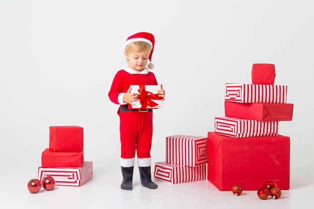 A toddler in a santa costume stands on a white background next to gift boxes for christmas. christmas concept, text space