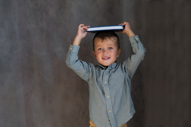 Toddler school boy with book on his head on gray wall