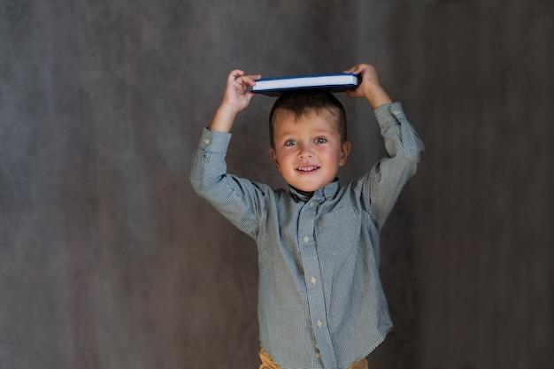 灰色の壁に頭に本を持っている幼児の男子生徒