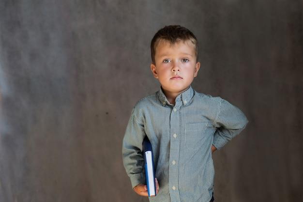 Маленький школьник с книгами на серой стене