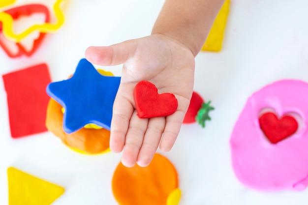 幼児は白いテーブルの上に着色された粘土から彫刻します。小さな子供の手が色の粘土の破片を絞ります。子供の創造性、教育ゲーム、細かい運動能力。塑像用粘土の心臓