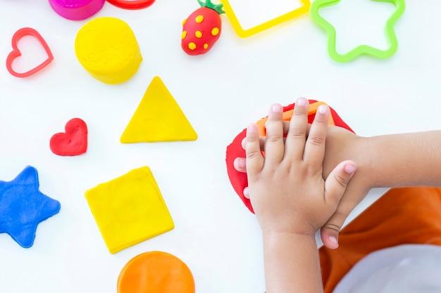 유아는 흰색 테이블에 색된 plasticine에서 조각합니다. 어린 아이의 손이 유색 플라스틱 조각을 짜냅니다. 어린이의 창의력, 교육용 게임, 미세 운동 기술