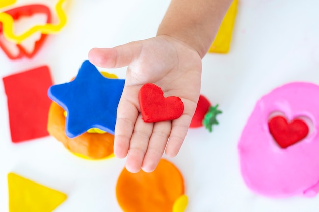 Toddler sculpts from colored plasticine on a white table. the hand of a small child squeezes pieces of colored plasticine. childrens creativity, educational games, fine motor skills. plasticine heart