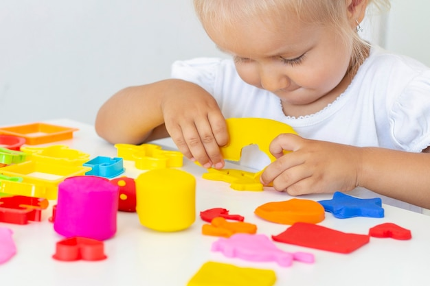 Toddler sculpts from colored plasticine on a white table. the hand of a small child squeezes pieces of colored plasticine. childrens creativity, educational games, fine motor skills