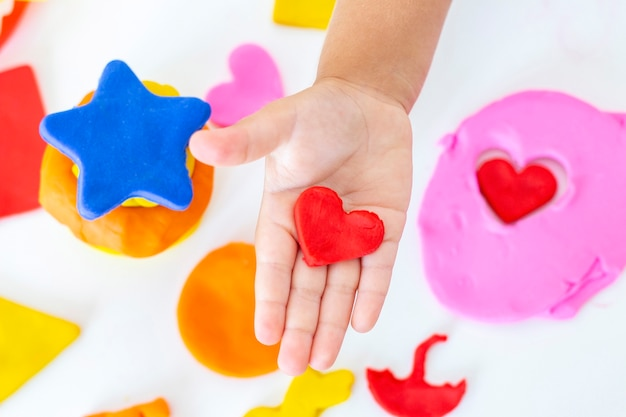 Toddler sculpts from colored plasticine on a white table.