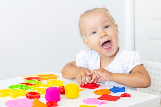 Toddler sculpts from colored plasticine on a white table