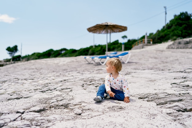 Toddler sits on the beach against the background of a sun lounge and looks to the side