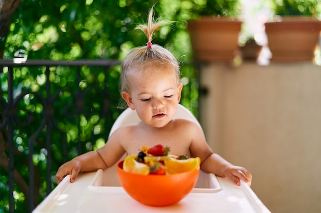 Toddler sits on a high chair on the balcony and looks at a bowl of fruit