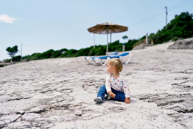 유아는 일광욕 라운지를 배경으로 해변에 앉아 옆을 바라보고 있습니다.