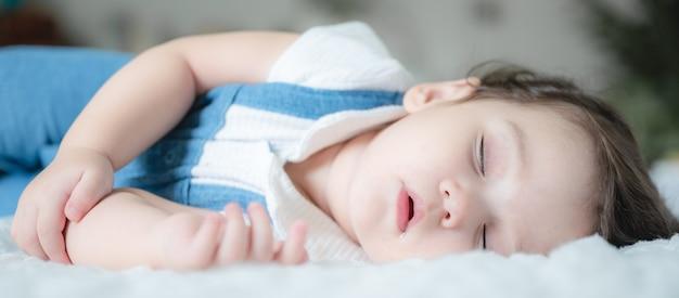 白いベッドで寝ている幼児