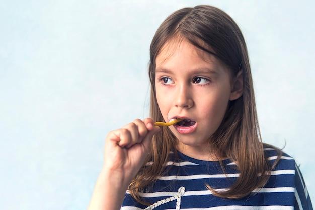 Малыш улыбается, чистя зубы. синий фон. маленькая девочка кавказской внешности чистит зубы зубной щеткой, гигиенические процедуры по утрам.