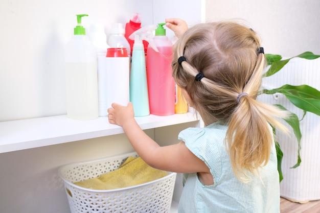Малыш трогает бутылки с бытовой химией, бытовыми чистящими средствами. опасная ситуация
