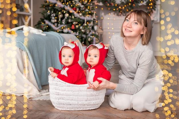赤いトナカイのサンタクロースの衣装を着た幼児の双子は、クリスマスツリーの背景に母親と一緒に家に座っています