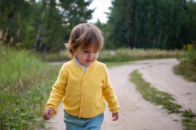 목장이나 숲속 농장의 황량한 시골길 시골 모래길을 혼자 걷는 유아