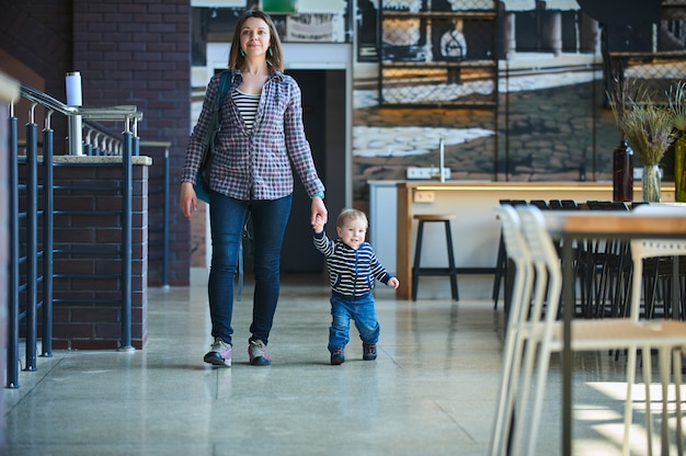 Toddler walking in the cafe with his mom.