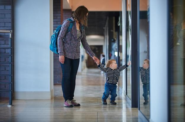 그의 엄마와 함께 쇼핑 센터에서 걷는 유아.