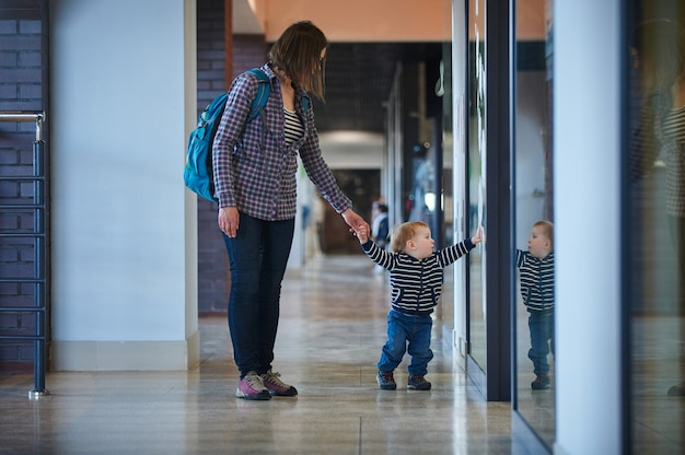 Toddler walking in the shopping center with his mom.