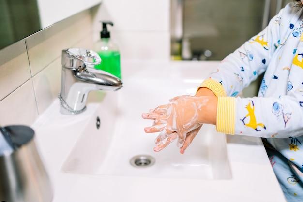 Covid 19 코로나 바이러스를 예방하고 예방하기 위해 비누로 손을 씻는 유아
