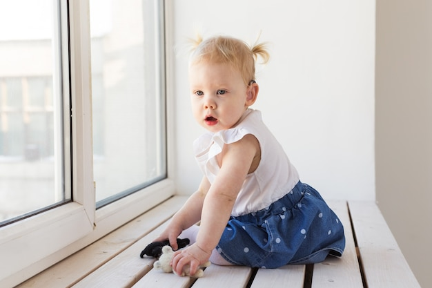 Toddler wearing a hearing aid at home