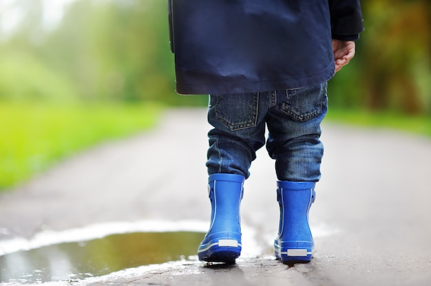 Toddler wearing rain boots standing near a puddle on the summer or autumn day