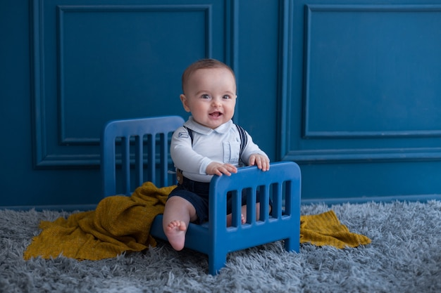 A toddler with elegant outfist inside decorative bed in the room.