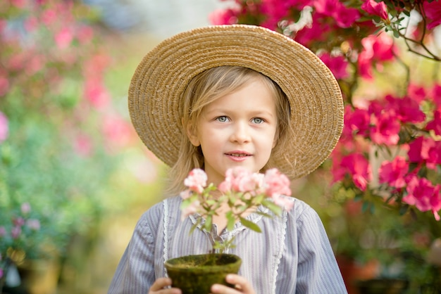 Toddler with flower basket. girl holding pink flowers