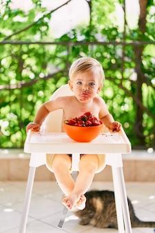 Малыш с грязным лицом сидит на высоком стульчике на балконе