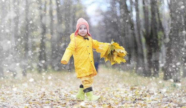가 공원에서 산책에 유아입니다. 가을 숲의 첫 서리와 첫 눈. 아이들은 눈과 나뭇잎으로 공원에서 놀고 있습니다.