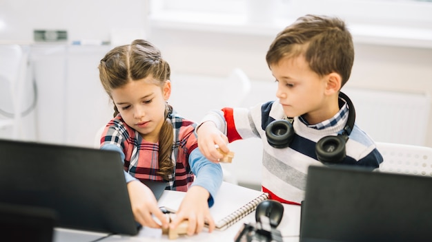 Toddlers playing with wooden blocks with laptop on desk