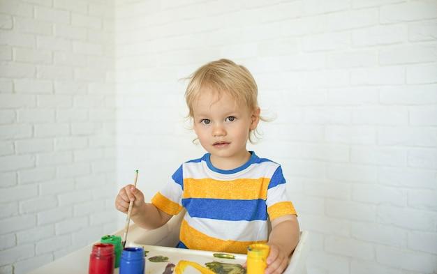 Малыш с развивающими игрушками для творчества. мальчик играет дома.