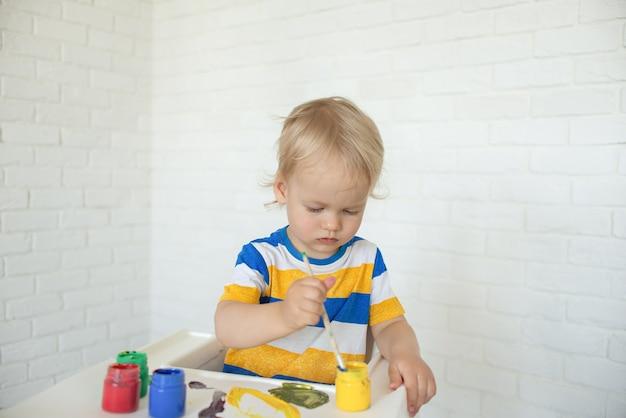 Малыш с развивающими игрушками для творчества. ребенок рисует красками, играет дома сидит у ребенка