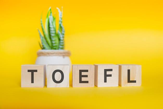 黄色の背景に木製のブロックで作られたtoeflメッセージ