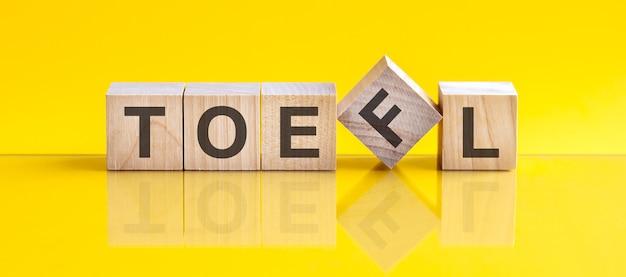 나무 블록에 쓰여진 토플 단어. 제안 단어는 노란색 테이블에 누워 있는 나무 빌딩 블록으로 만들어집니다. 교육 개념입니다. 토플 - 외국어로서의 영어 시험의 줄임말