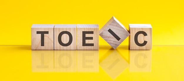 Toeic 단어는 노란색 테이블에 누워 있는 나무 빌딩 블록으로 만들어집니다.