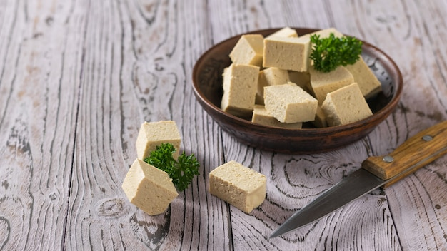 Tofu cheese in a clay bowl and a knife on a wooden surface. soy cheese. vegetarian product.