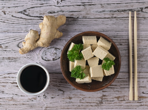 Tofu cheese in a clay bowl with ginger root on a wooden table. soy cheese. vegetarian product. flat lay.